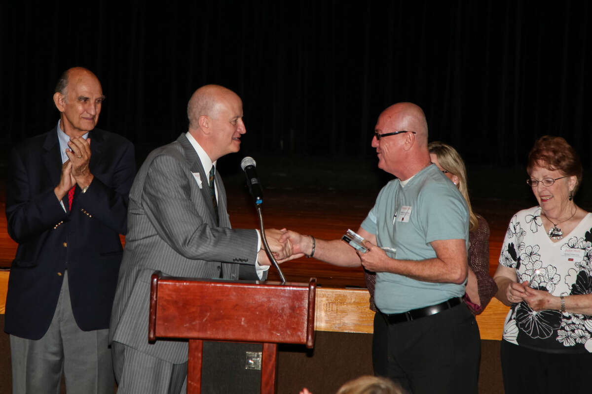 Danny Holeva, executive director of Arts Council of Midland, left, congratulates Michael Fields after the Midland Community Theatre volunteer was named Volunteer of the Year Tuesday at the council's annual meeting. Looking on are volunteers Tom Hyde, far left, and Julia Still, far right.