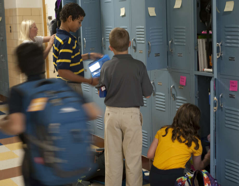 Students rush to class and put their school notebooks in lockers Wednesday on the first day back to school. Tim Fischer\Reporter-Telegram Photo: Tim Fischer\Reporter-Telegram