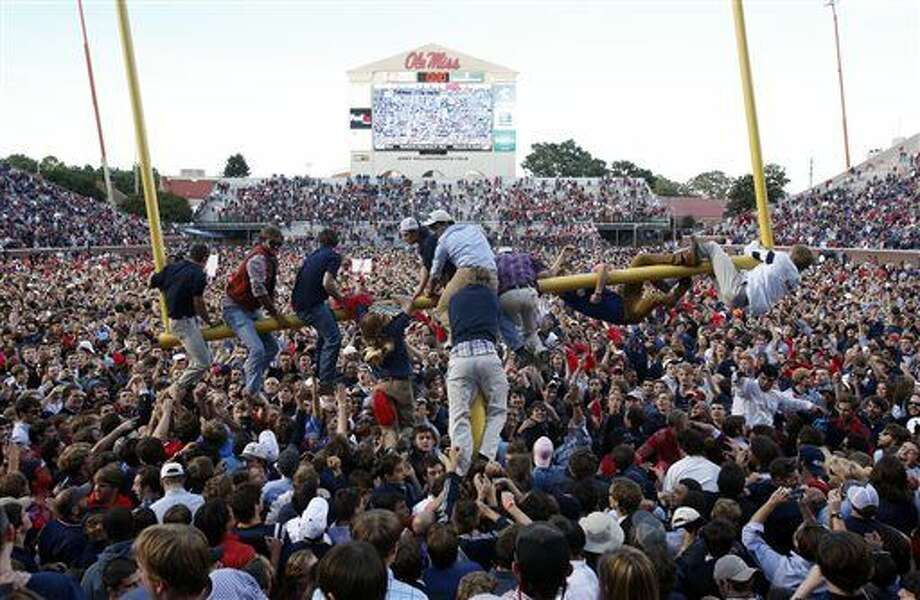 Mississippi fans gather on the field, as some clamber onto a goal post, after Mississippi defeated Alabama 23-17 in an NCAA college football game in Oxford, Miss., on Saturday Oct. 4, 2014. (AP Photo/Tuscaloosa News, Robert Sutton) Photo: Robert Sutton