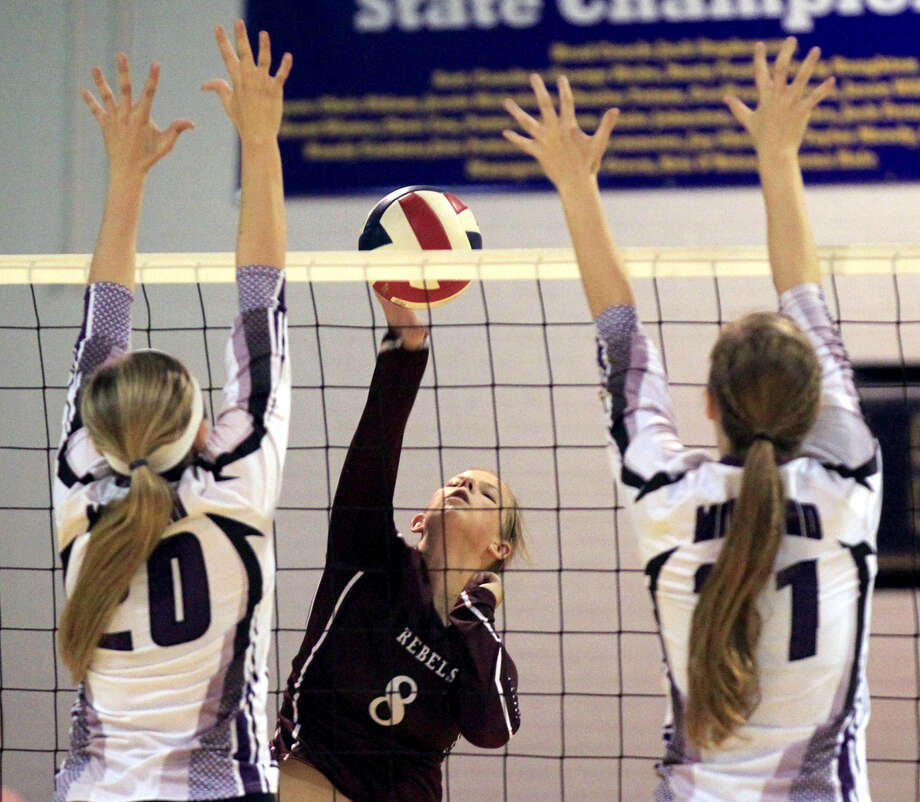 Midland High's Claire Lancaster (20) and Krista Epley (21) try to block an attack from Lee's Madison Petrich (8) on Oct. 4 at MHS. James Durbin/Reporter-Telegram Photo: James Durbin
