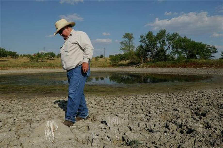 In this photo taken Aug. 1, 2011, Pete Bonds stands near a shrinking stock tank on his ranch in Saginaw, Texas. Bonds said that he normally ran 400 head of cattle on his 5,000 acre ranch but because of the drought he was down to 300. Photo: Rex C. Curry/Associated Press / FR41626AP