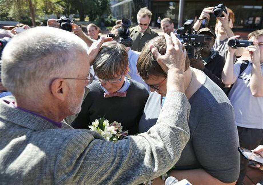 Rev. Robin Gorsline, left, marries Nicole Pries, second from left, and Lindsey Oliver, one of the first same-sex couples in Virginia to be married Oct. 7 at a Richmond court building in Richmond, Va. Photo: Steve Helber/Associated Press