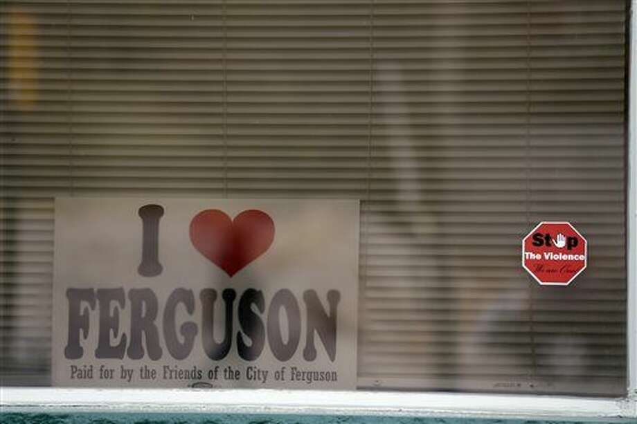 FILE - In this Nov. 26, 2014 file photo, a Stop The Violence sticker is displayed on the window of a Ferguson, Mo., business along with a sign in support of the city. A year after parts of Ferguson burned in the anger that followed a grand jury's decision not to prosecute the police officer who fatally shot Michael Brown, there are signs of hope. Some businesses are back in operation, barricades are down and the two-thirds black St. Louis suburb led almost exclusively by whites a year ago now has a black voice in city government. (AP Photo/Jeff Roberson, File) Photo: Jeff Roberson