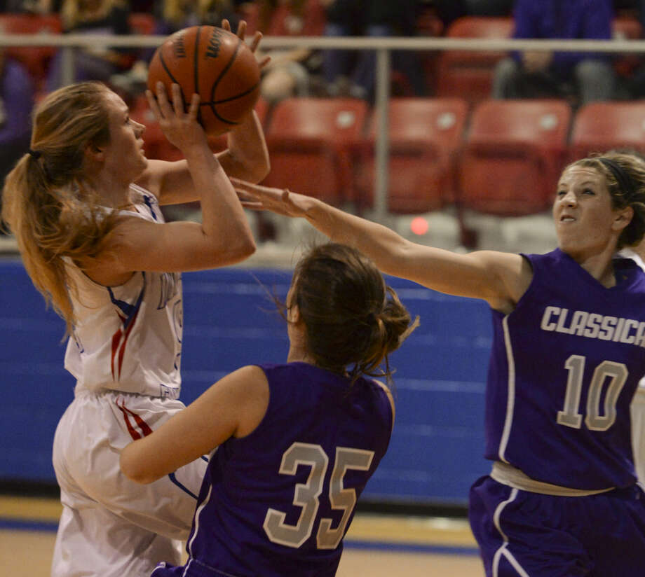 Midland Christian's Megan Ashton drives the lane as Midland Classical's Makenna Beattie, 35 is called for a block as Alissa Beattie, 10, helps defend Monday 11-23-2015 at the McGraw Events Center on Midland Christian campus. Tim Fischer\Reporter-Telegram Photo: Tim Fischer