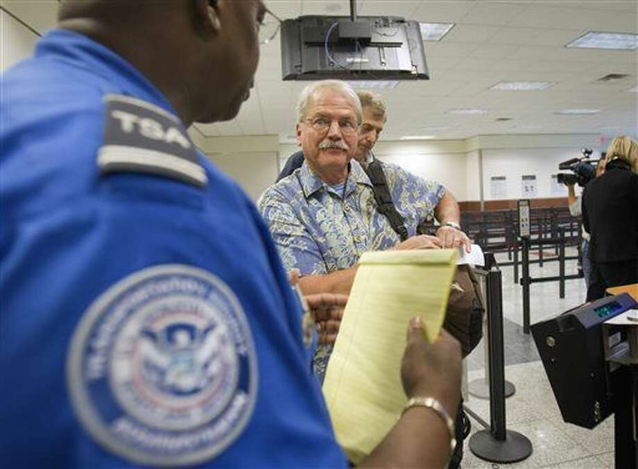 FILE - In this Oct. 4, 2011 file photo, passenger Don Heim, right, of Alpharetta, Ga., is briefed by Transportation Security Administration trainer Byron Gibson before going through a new expedited security line at Hartsfield-Jackson International Airport in Atlanta. The news that a man flew from Liberia to the U.S. after exposure to Ebola, and wound up in a hospital isolation ward, has led to calls for tougher measures to protect Americans, such as a ban on flights from countries hit by the epidemic. Federal health officials and airlines have dismissed any risk to passengers who flew with the man last month and say they are protecting travelers by screening passengers and wiping down airplane cabins nightly. (AP Photo/David Goldman) Photo: David Goldman\Associated Press