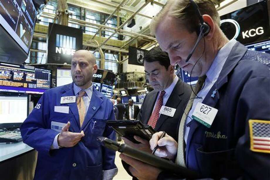Specialist Meric Greenbaum, left, works with traders Mark Muller, center, and Michael Smyth at his post on the floor of the New York Stock Exchange, Tuesday, Nov. 24, 2015. Stocks are opening modestly lower, following declines in Europe. (AP Photo/Richard Drew) Photo: Richard Drew