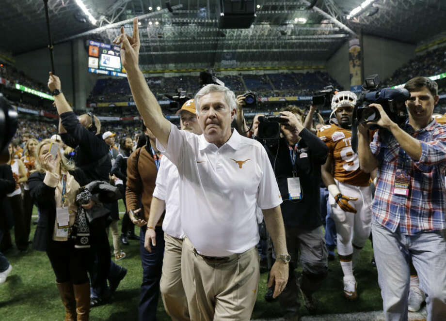 "Texas coach Mack Brown, center, holds up the ""Hook' em Horns"" sign as he sings the school song following the Valero Alamo Bowl Monday, Dec. 30, 2013, in San Antonio. The man credited with the creation of the sign, Harley Clark, died Thursday. (AP Photo/Eric Gay) Photo: Eric Gay"