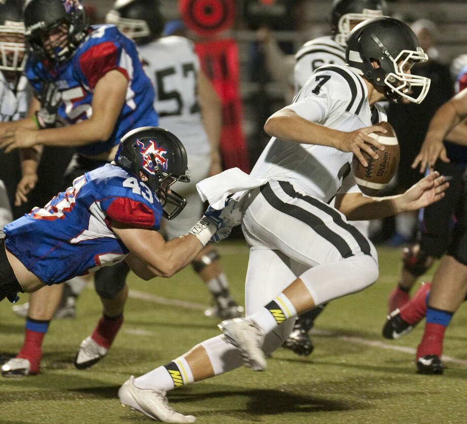 Midland Christian's Will Sanford holds on to bring down Dallas Bishop's QB Tristan Smith Friday at Mustang Field. Tim Fischer\Reporter-Telegram Photo: Tim Fischer