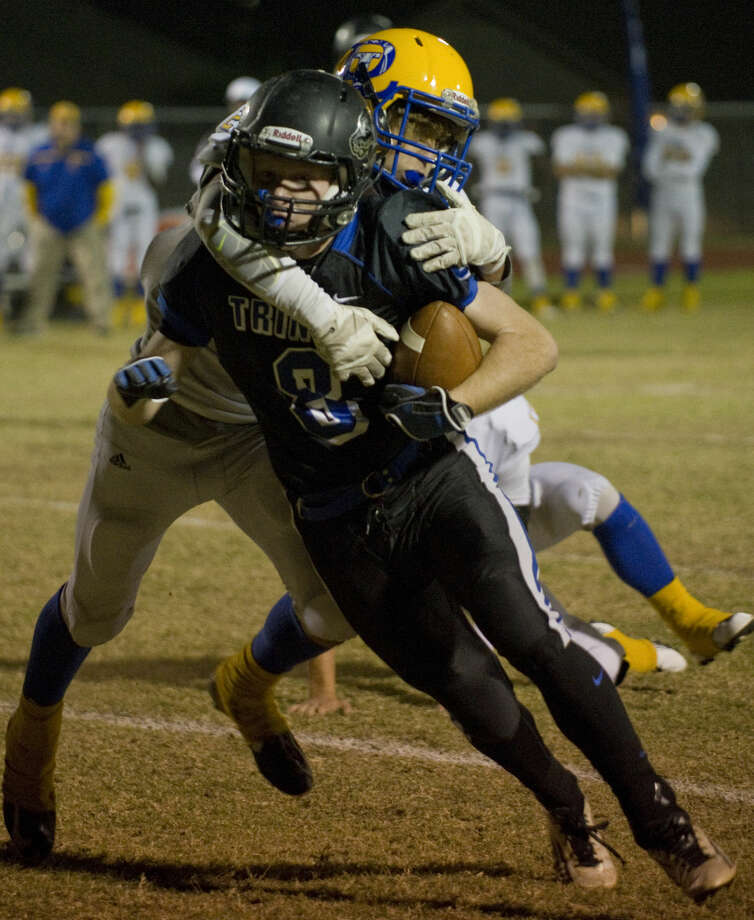 Trinity's Peyton Harrington tries to gain more yardage as Dallas Lutheran's Cody Patterson hangs on Friday 11-6-2015 at Coombes Field. Tim Fischer\Reporter-Telegram Photo: Tim Fischer
