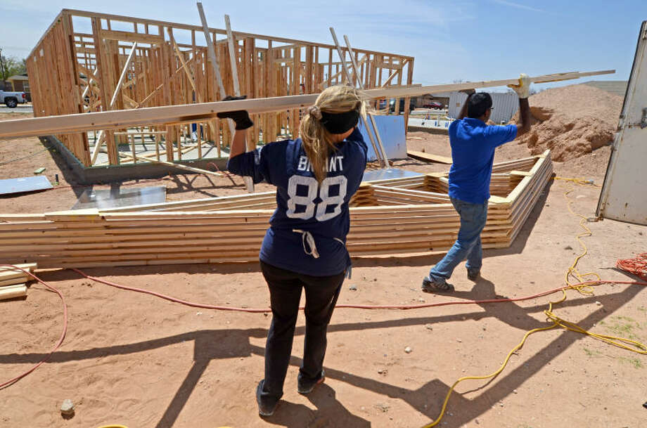 Concho employees Stephanie Wilson and Venu Yankarla carry part of a roof frame while building a Habitat for Humanity house Saturday. Concho Operating Group donated funds to build a Habitat home. James Durbin/Reporter-Telegram Photo: James Durbin