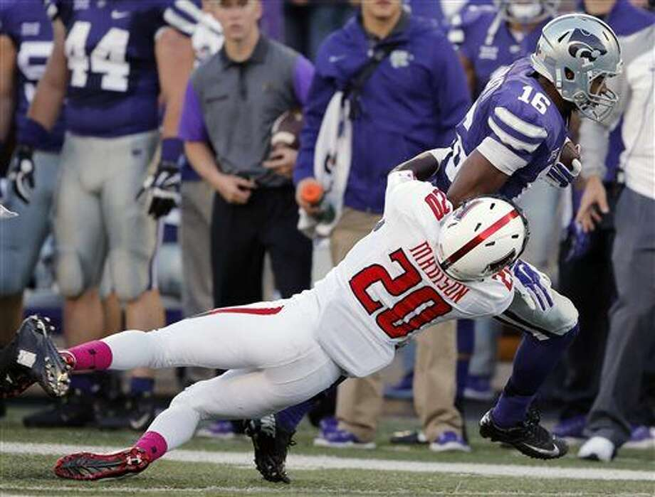 Kansas State wide receiver Tyler Lockett (16) is tackled by Texas Tech defensive back Tevin Madison (20) during the first half of an NCAA college football game in Manhattan, Kan., Saturday, Oct. 4, 2014. (AP Photo/Orlin Wagner) Photo: Orlin Wagner