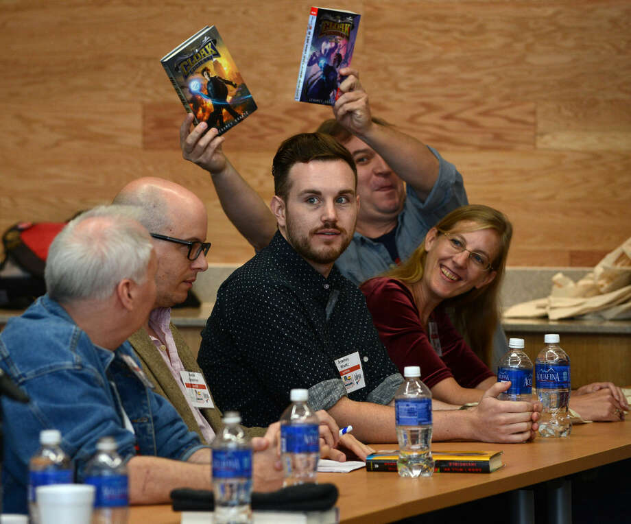 """Jeramy Kraatz of Odessa, center, is introduced during a panel discussion """"Bang! Pow! Zoom!"""" with authors offering their views on writing about super heroes that was one of several presentations that were part of Books in the Basin Saturday at Odessa College. Photo: Mark Sterkel 