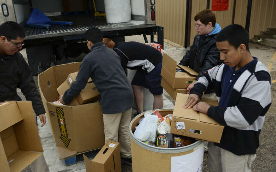 Midland Academy Charter School 7th and 8th graders load the nearly 2000 cans of food collected into containers for the West Texas Food Bank. Tim Fischer\Reporter-Telegram Photo: Tim Fischer