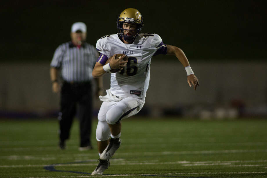 Midland's quarterback Ryan Goodrum runs the ball for a first down Friday night during the second quarter of their game at Ratliff stadium. Photo: Courtney Sacco