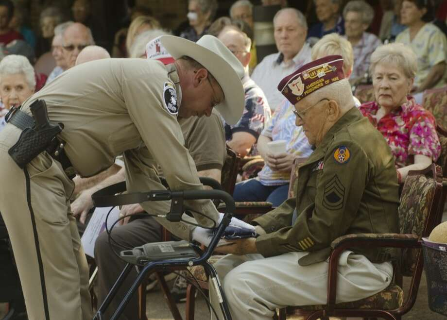Deputy Mike Naylor, Midland Sheriff Department Honorguard Commander, presents the American Flag to Andy Kauffman, USAF WWII Veteran and POW, at the Honor our Veterans ceremony Friday at Manor Park. Photo by Tim Fischer/Midland Reporter-Telegram Photo: Tim Fischer