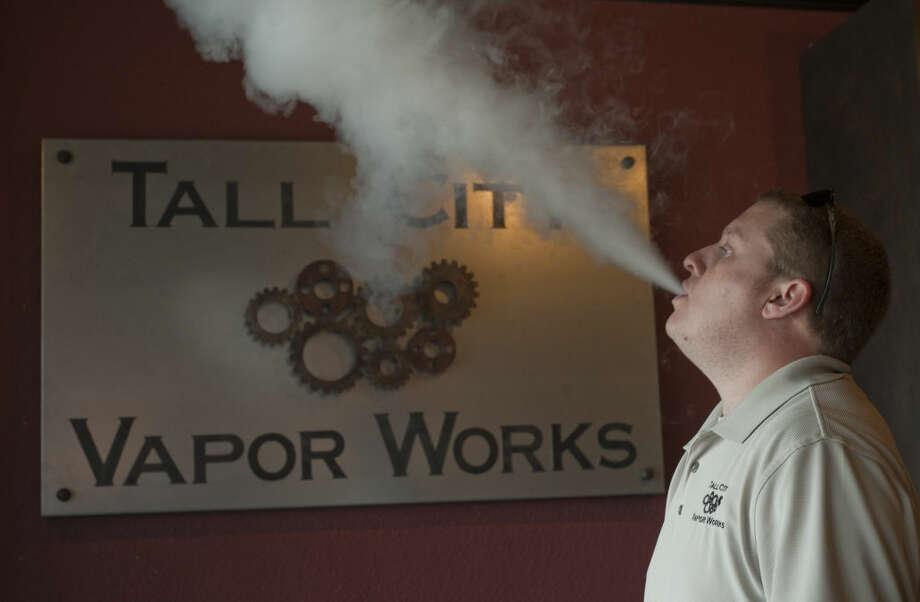 Brian Evans, owner of Tall City Vapor Works, blows a cloud of vapor in the shop. Tim Fischer\Reporter-Telegram Photo: Tim Fischer