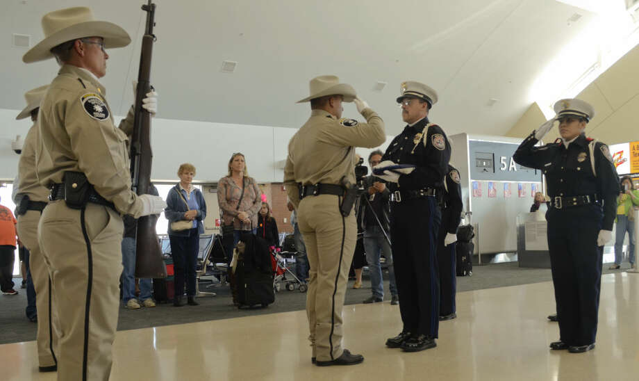 Members of Midland Police Department Honor guard present the U.S. Honor Flag to Midland County Sheriff Officers Honor Guard as they escort the U.S. Honor Flag Monday after it arrived on a flight from Dallas to be present at the funeral of MCSO Sgt. Mike Naylor today. Tim Fischer\Reporter-Telegram Photo: Tim Fischer