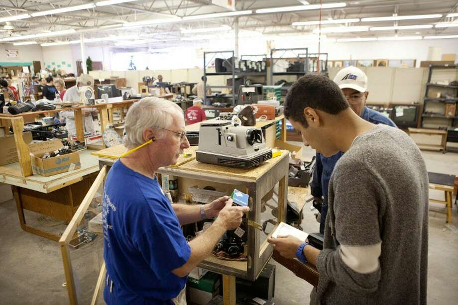 Craig Tellinghuisen, left, assists Ernesto Macias, 17, with finding film for a camera he's purchasing Saturday at the Texas Size Garage Sale. Cindeka Nealy/Reporter-Telegram Photo: Cindeka Nealy