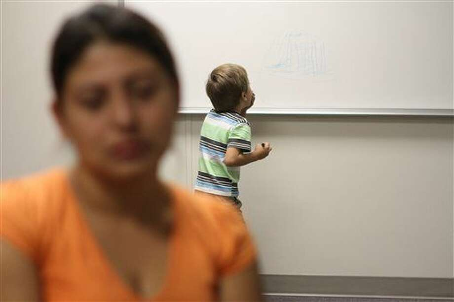 FILE - In this Sept. 10, 2014, file photo, an unidentified immigrant from Guatemala who declined to give her name, is interviewed, while her son paints on a whiteboard at the Artesia Family Residential Center, a federal detention facility for undocumented immigrant mothers and children in Artesia, N.M. The facility is now releasing more detainees rather than deporting them, according to Artesia Mayor Phillip Burch. (AP Photo/Juan Carlos Llorca, File) Photo: Juan Carlos LLorca
