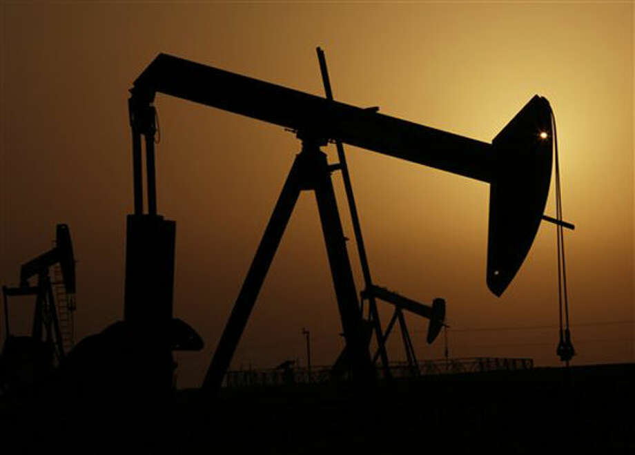 Oil pumps work at sunset in the desert oil fields of Sakhir, Bahrain on Oct. 14.  Photo: Hasan Jamali