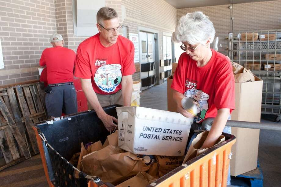 FILE - John Crooks, left, and Cindy Rice, with the West Texas Food Bank, sort through boxes of non-perishable items collected during the Stamp Out Hunger Food Drive, May 14 at the U.S. Post Office on Veterans Airpark Lane. Cindeka Nealy/Reporter-Telegram Photo: Cindeka Nealy