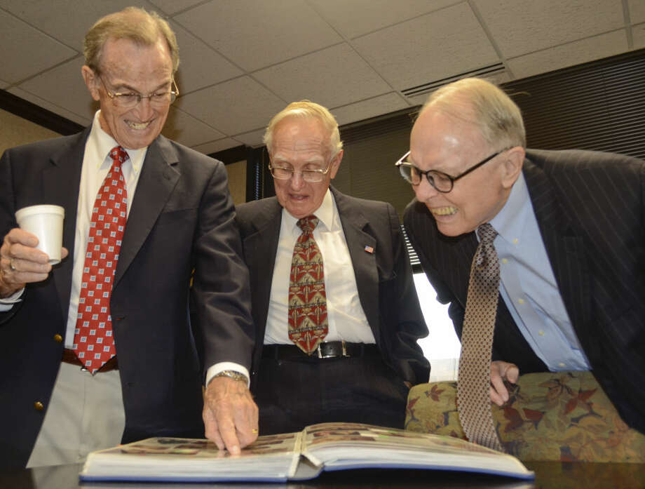 Bob Bledsoe, Charles Tighe and Bob Dawson look over old photos from their begining days as they celebrate 40 years with Cotton, Beldsoe, Tighe and Dawson Law firm. Tim Fischer\Reporter-Telegram Photo: Tim Fischer