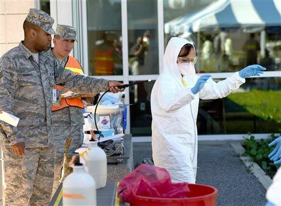 Staff Sgt. Dwight Thomas, left, sprays a bleach mixture on a protective suit worn by Airman 1st Class Jamela Shannon on Wednesday, Oct. 22, 2014, during an infectious disease training exercise for the Ebola virus on Eglin Air Force Base, Fla. Medical specialists on base perform the exercise with a different disease each year. (AP Photo/Northwest Florida Daily News, Nick Tomecek) Photo: Nick Tomecek
