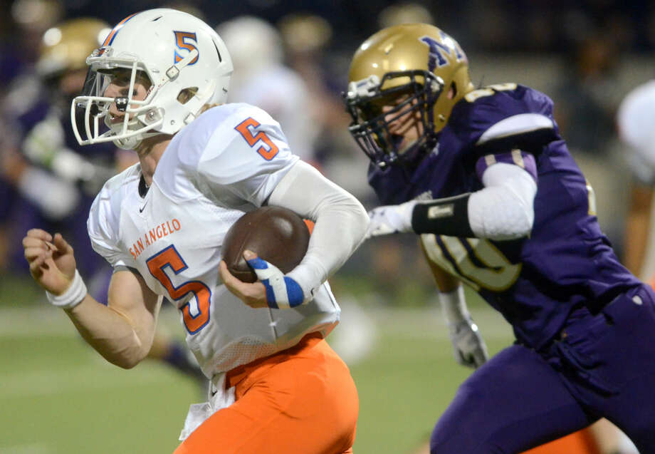 San Angelo Central quarterback Braden Hucks (5) runs the ball against Midland High's Jack Youngblook (40) on Friday at Midland High. James Durbin/Reporter-Telegram Photo: James Durbin