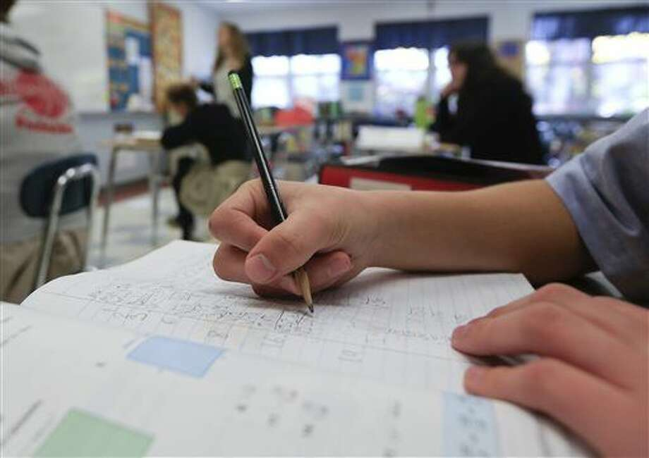 "In this Tuesday, Nov. 17, 2015 photo, a student works in an eight grade algebra class at Holy Spirit School in East Greenbush, N.Y. The Diocese of Albany, New York, announced recently that it will reduce the frequency of the Common Core-aligned tests while sticking with the standards. The decision coincides with a call by New York Gov. Andrew Cuomo for ""a total reboot"" of the Common Core after his state became the epicenter of anti-testing sentiment. (AP Photo/Mike Groll) Photo: Mike Groll"