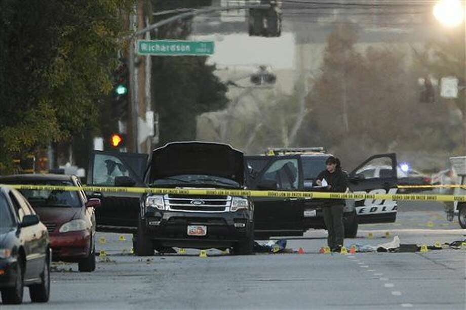 An investigator looks at a Black SUV that was involved in a police shootout with suspects, Thursday, Dec. 3, 2015, in San Bernardino, Calif. A heavily armed man and woman opened fire Wednesday on a holiday banquet, killing multiple people and seriously wounding others in a precision assault, authorities said. Hours later, they died in a shootout with police. (AP Photo/Jae C. Hong) Photo: Jae C. Hong