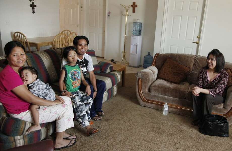 The Thang family sit with case worker Ida Flecher of Casa de Amigos while talking about the move into their house in Midland. Chaney Mitchell/Reporter-Telegram Photo: Chaney Mitchell