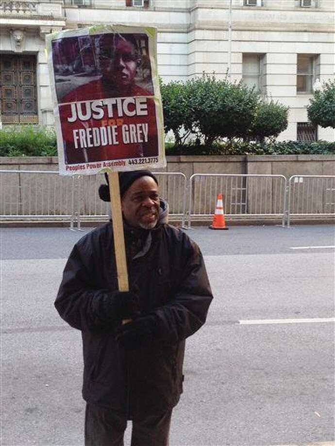 Demonstrator Arthur Johnson carries a sign advocating justice for Freddie Gray on Monday, Dec. 7, 2015, outside the courthouse in Baltimore where the trial of Offcer William Porter enters its second week. (AP Photo/David Dishneau) Photo: David Dishneau