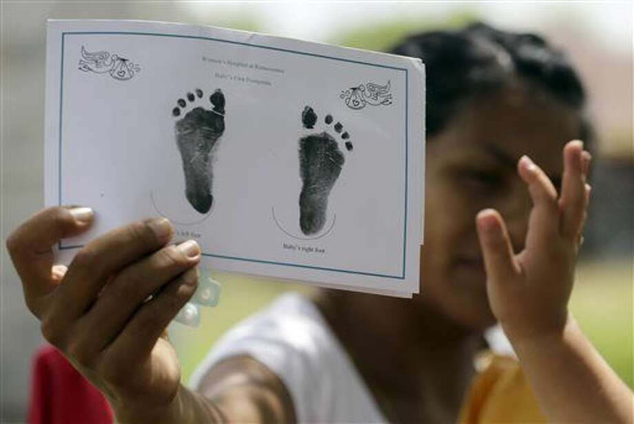 In this Sept. 16, 2015, photo, a woman in Sullivan City, Texas, who said she entered the country illegally shows the footprints of her daughter, reaching into photo, who was born in the United States, but was denied a birth certificate. Texas has for seven years said it won't accept Mexican identification cards when issuing birth certificates for children of people in the United States illegally. But it doesn't appear to have stepped up enforcement until recently, amid mounting political pressure to get tougher on immigration, documents obtained by The Associated Press show. (AP Photo/Eric Gay) Photo: Eric Gay