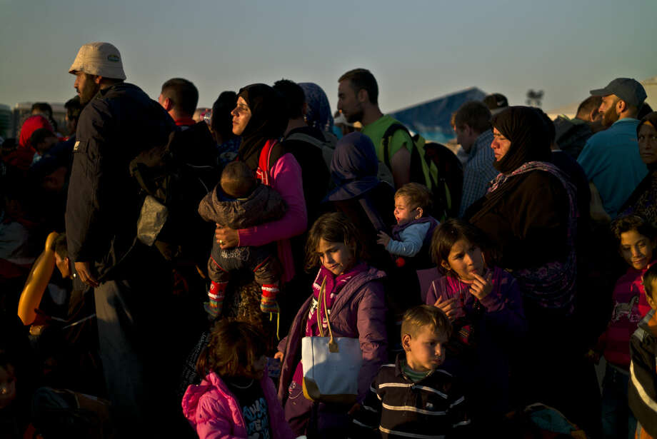 Syrian people line up to board a bus that will take them to the center for asylum seekers, after crossing the Serbian-Hungarian border near Roszke, southern Hungary, Saturday, Sept. 12, 2015. Hundreds of thousands of Syrian refugees and others are still making their way slowly across Europe, seeking shelter where they can, taking a bus or a train where one is available, walking where it isn't. (AP Photo/Muhammed Muheisen) Photo: Muhammed Muheisen