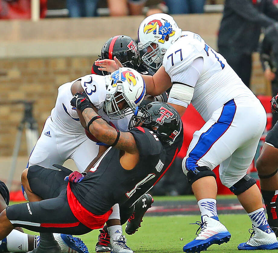 Texas Tech linebacker Pete Robertson (10) stops Kansas running back De'Andre Mann for no gain in Saturday's BIG XII contest between the Red Raiders and Jayhawks. Photo: Wade H Clay
