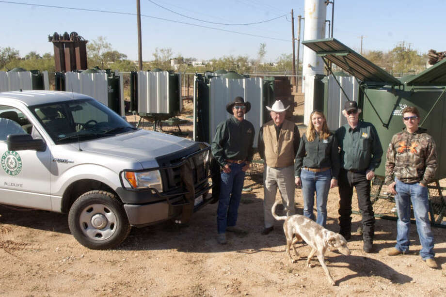 Mule Deer Foundation members Bobby Builta, co-chairman, Al Mitchell, Ret. Texas Ranger, Annaliese Scoggin of Texas Parks & Wildlife, Grier Brunson, co-chairman, and Greg Tomlin, advertising chairman, pose for a group photo with twelve 500-gallon drinker units that collect rainwater for mule deer to drink. Suzie, a two-year old tracking dog Photo: Midland Reporter-Telegram