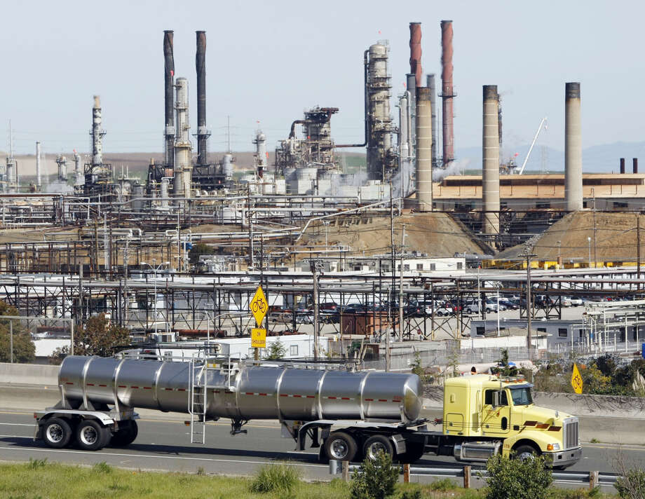 This March 9, 2010 file photo shows a tanker truck driving by the Chevron oil refinery in Richmond, Calif. The Obama administration is moving forward with a dramatic reduction in sulfur in gasoline and tighter emissions standards for cars, arguing the move will eventually save thousands of lives per year. The oil and gas industry warns the Environmental Protection Agency rules are unnecessary and will drive up gas prices. The rules will also add to the cost of buying a car. (AP Photo/Paul Sakuma, File) Photo: Paul Sakuma