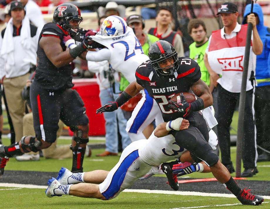 Tech running back DeAndre Washington drags a Kansas defender as he heads downfield for the Red Raiders in Saturday's Big XII action. Photo: Wade H Clay