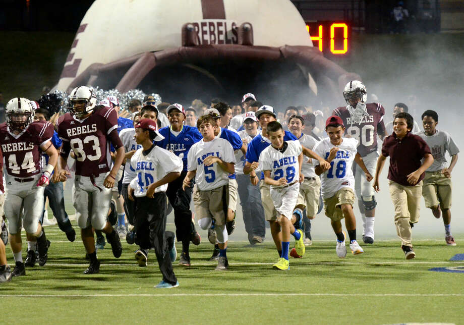 Abell and Alamo junior high football players run onto the field with Lee High players before the game against Abilene High on Friday at Grande Communications Stadium. James Durbin/Reporter-Telegram Photo: James Durbin