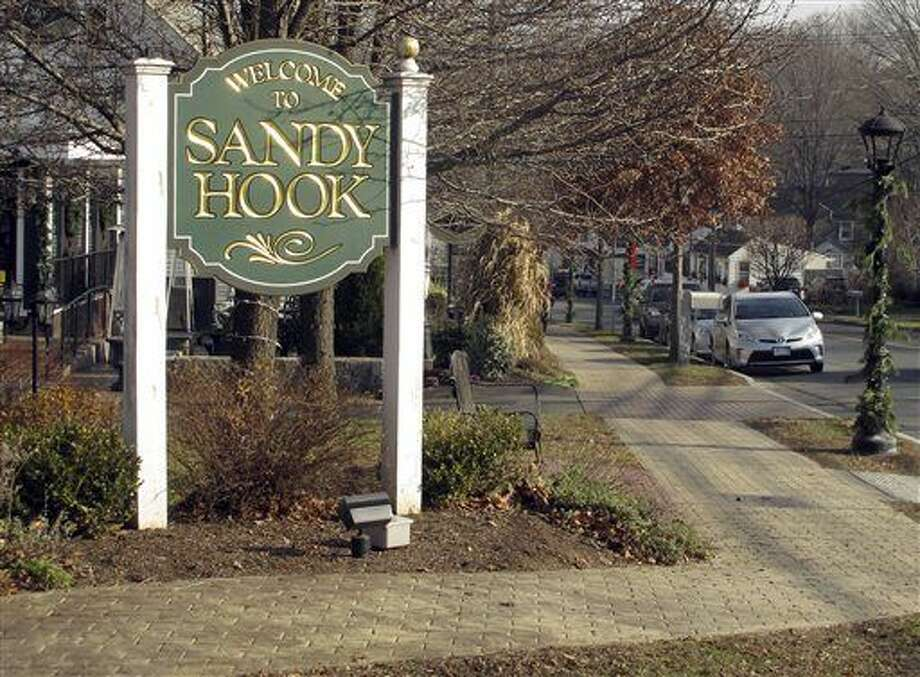 In this Friday, Dec. 11, 2015 photo, a sign welcomes people to the village of Sandy Hook in Newtown, Conn. An interfaith service is planned Monday evening, Dec. 14, on the third anniversary of the shooting at Sandy Hook Elementary School that killed 20 first-graders and six educators. Monday is also the first time the anniversary falls on a school day. (AP Photo/Dave Collins) Photo: Dave Collins