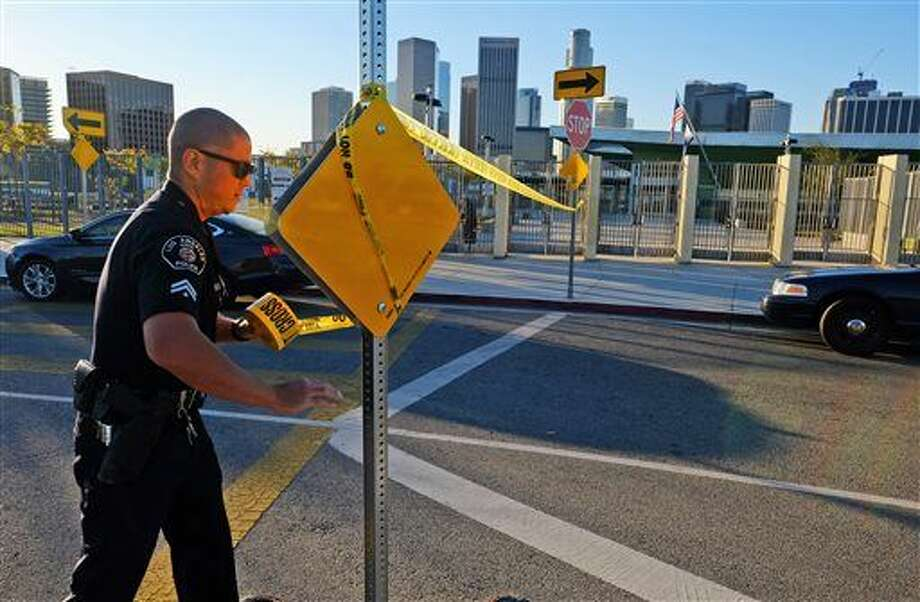 A police officer puts up yellow tape to close the school outside of Edward Roybal High School in Los Angeles, on Tuesday morning, Dec. 15, 2015. All schools in the vast Los Angeles Unified School District, the nation's second largest, have been ordered closed due to an electronic threat Tuesday. (AP Photo/Richard Vogel) Photo: Richard Vogel