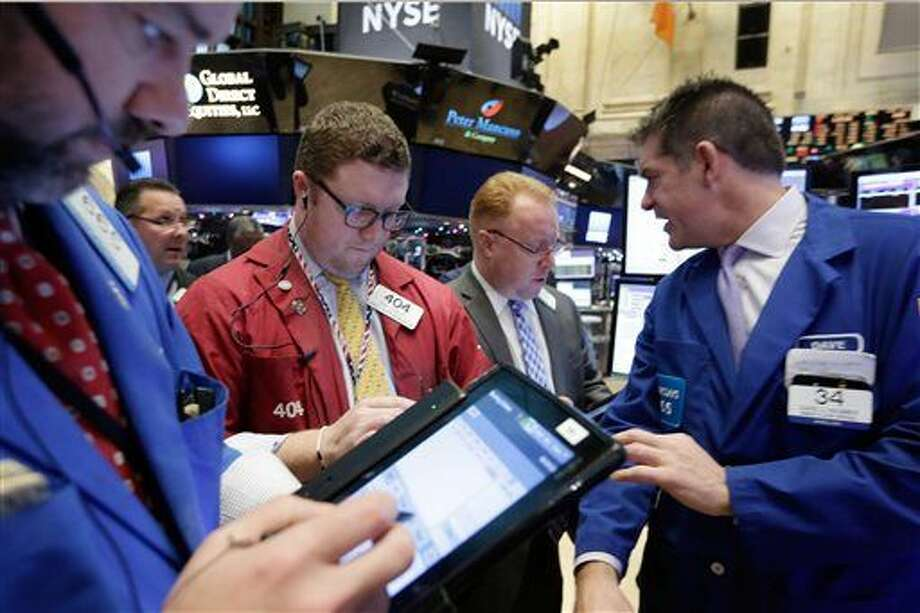 Specialist David Haubner, right, works with traders on the floor of the New York Stock Exchange, Monday, Dec. 14, 2015. U.S. stocks are edging lower in early trading as the market comes off its biggest weekly decline since the summer. (AP Photo/Richard Drew) Photo: Richard Drew