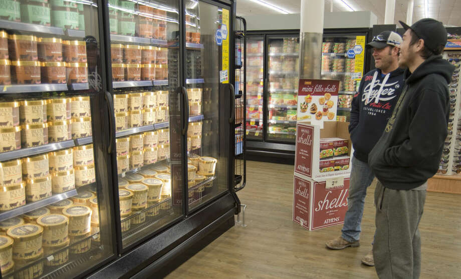 Steve Morris and his son Dylan look over the choices of Blue Bell ice cream Monday 12-14-2015 after the ice cream was restocked on Midland shelves early Monday at Market Street. Tim Fischer\Reporter-Telegram Photo: Tim Fischer