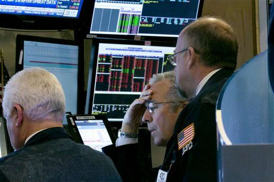 Trader Thomas Kay, center, works with colleagues at their booth on the floor of the New York Stock Exchange, Friday, Dec. 11, 2015. Stocks are sharply lower in midday trading, led by more declines in energy and materials stocks as prices for oil and other commodities slide. (AP Photo/Richard Drew)) Photo: Richard Drew