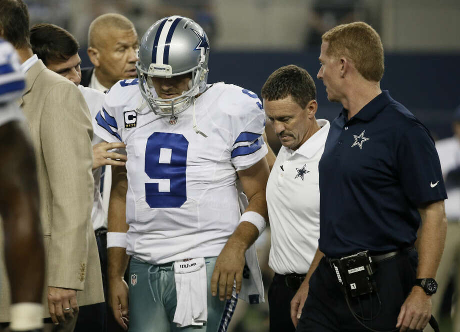 Dallas Cowboys head coach Jason Garrett, right, and team medical staff help Tony Romo (9) off the field after Romo was injured on a sack by Washington Redskins' Keenan Robinson during the second half of an NFL football game, Monday, Oct. 27, 2014, in Arlington, Texas. (AP Photo/Brandon Wade) Photo: Brandon Wade