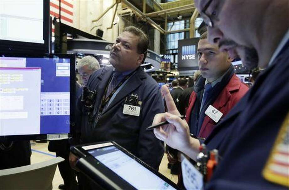 Traders John Santiago, left, and Gino Risignano, center, work on the floor of the New York Stock Exchange, Tuesday, Dec. 15, 2015. Stocks are climbing in early trading as buyers return to a market that has been mostly beaten down in recent days. (AP Photo/Richard Drew) Photo: Richard Drew