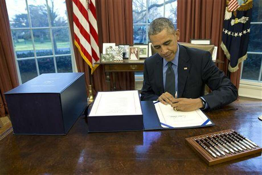 President Barack Obama signs the budget bill in the Oval Office of the White House, Friday, Dec. 18, 2015, in Washington. (AP Photo/Carolyn Kaster) Photo: Carolyn Kaster