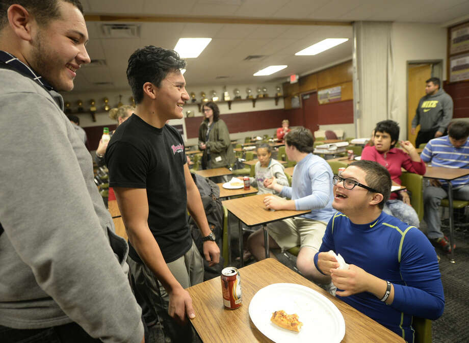 From left, Lee High football players James Nieto and Daniel Parra talk with Lee student Carlos Neria during a pizza party for the team and special needs students to celebrate nearly 100 toys being donated to Toys For Cops by Lee students, Tuesday, Dec. 15, 2015. James Durbin/Reporter-Telegram Photo: James Durbin
