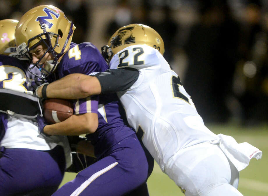 Midland High's Chandler Berrones (4) is wrapped up by Abilene High's Hill Holloway (22) on Friday at Grande Communications Stadium. James Durbin/Reporter-Telegram Photo: James Durbin