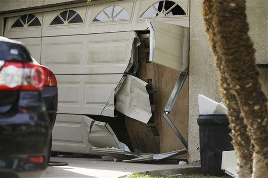 FILE - In this Dec. 9, 2015 file photo, a garage door of Enrique Marquez's home is broken in after an FBI raid, in Riverside, Calif. Marquez a former security guard who bought the assault rifles used by his friend in the San Bernardino massacre, was expected to be charged as early as Thursday, according to two law enforcement officials. The specific federal charges against Marquez were not immediately clear.(AP Photo/Jae C. Hong,File) Photo: Jae C. Hong